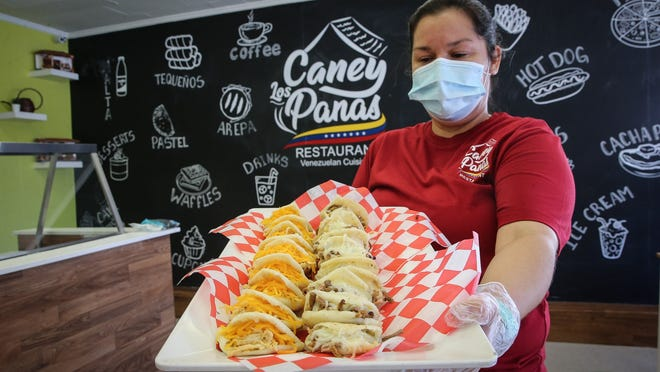 Owner Carla Palencia shows some freshly made arepas at the newly opened Caney Los Panas at 20 Exchange St. in Milford on Thursday.