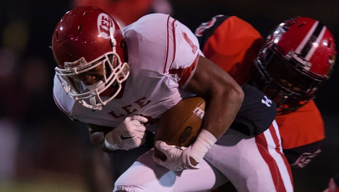 Lee's Daimion Wright is tackled by Central's Toron Morten during the AHSAA Class 7A quarterfinal playoff game on Friday, Nov. 13, 2015, in Phenix City, Ala.