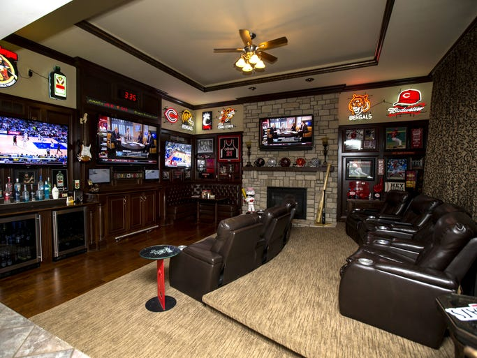 Formerly the family room, the Gregors' media room has 16-foot ceilings, five televisions, a sports news ticker system, eight theater seats with lighted cupholders, a fireplace and full bank of floor-to-ceiling windows (behind the curtains at left).