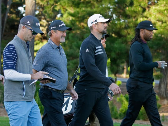 From left, golfers Kevin Streelman, Jerry Kelly, and NFL football player Aaron Rodgers and Larry Fitzgerald make their way down the first fairway of the Spyglass Hill Golf Course during the first round of the AT&T Pebble Beach National Pro-Am golf tournament Thursday, Feb. 8, 2018, in Pebble Beach, Calif. (AP Photo/Eric Risberg)