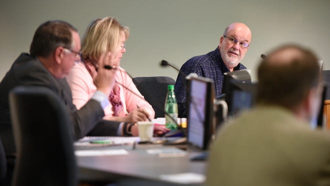 St. Cloud City Council President Jeff Goerger, right, talks with council members Steve Laraway and Carol Lewis during a City Council meeting in March.