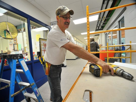 Construction worker Larry Berens, of Wausau, reaches for his driller to work on a ceiling job Tuesday afternoon, Sept. 23, 2014, at the Woodson YMCA in downtown Wausau.