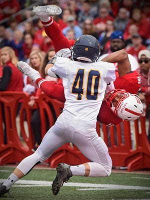 Antoine Taylor of St. John's University goes airborne to score a touchdown during the first half Saturday against Carleton at Clemens Stadium in Collegeville.