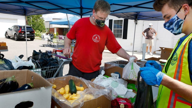 Volunteer Cameron Kasparian, right, assists Kevin Spliid in bagging fresh vegetables during a Wednesday visit to the food pantry at St. Philip Church, in Smithfield.
