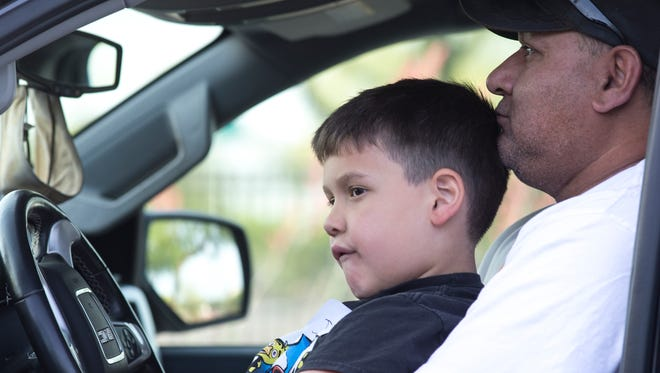 First-grader Jadyen Martinez and his grandfather Abe Granillo wait for the Webster Recreation Center to open in Mesa.