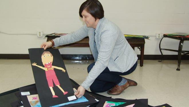 Jennifer Bush organizes artwork for A Playground of Color exhibit.