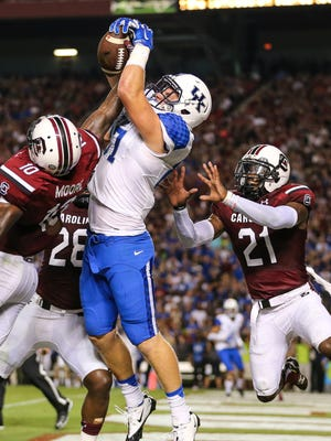 Kentucky Wildcats tight end C.J. Conrad (87) leaps for a pass in the end zone that is broken up by South Carolina Gamecocks linebacker Skai Moore (10) and safety Isaiah Johnson (21) during the second quarter at Williams-Brice Stadium.