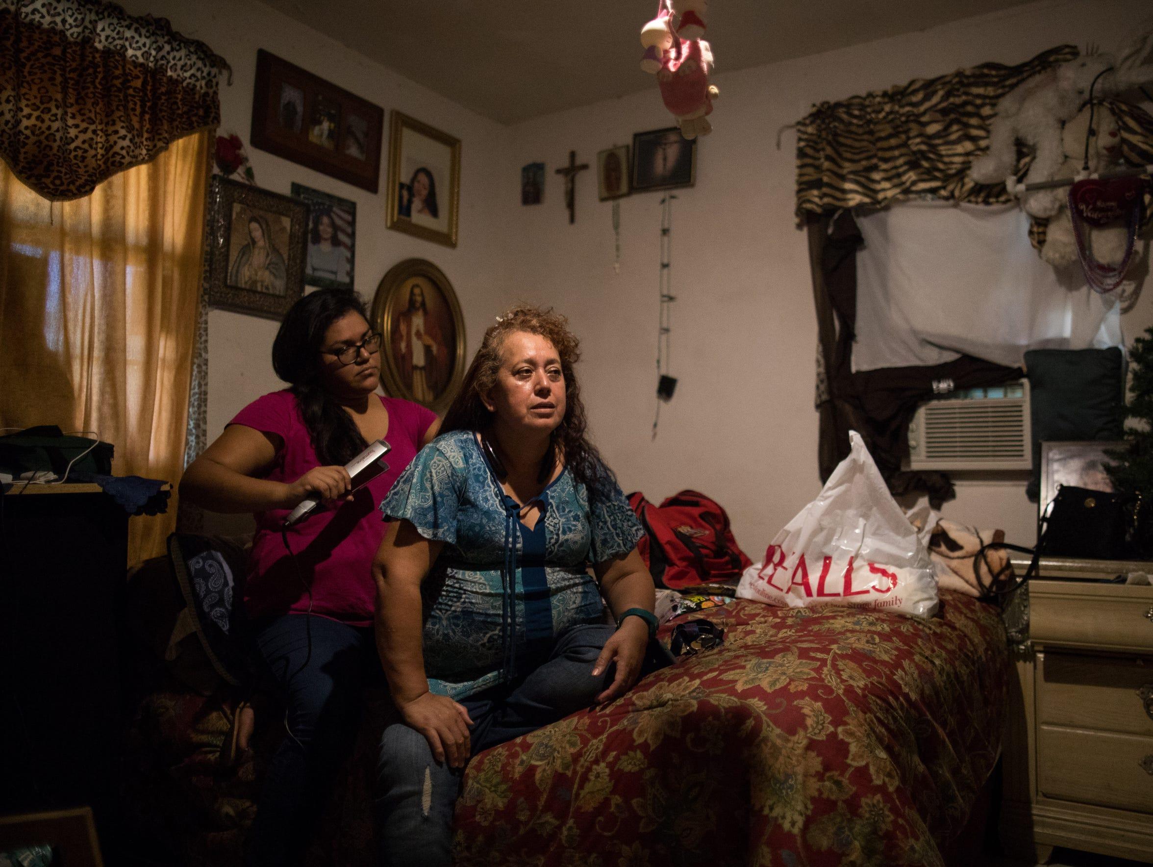 Maria Hernadez straightens her mother Carlota Palomo's