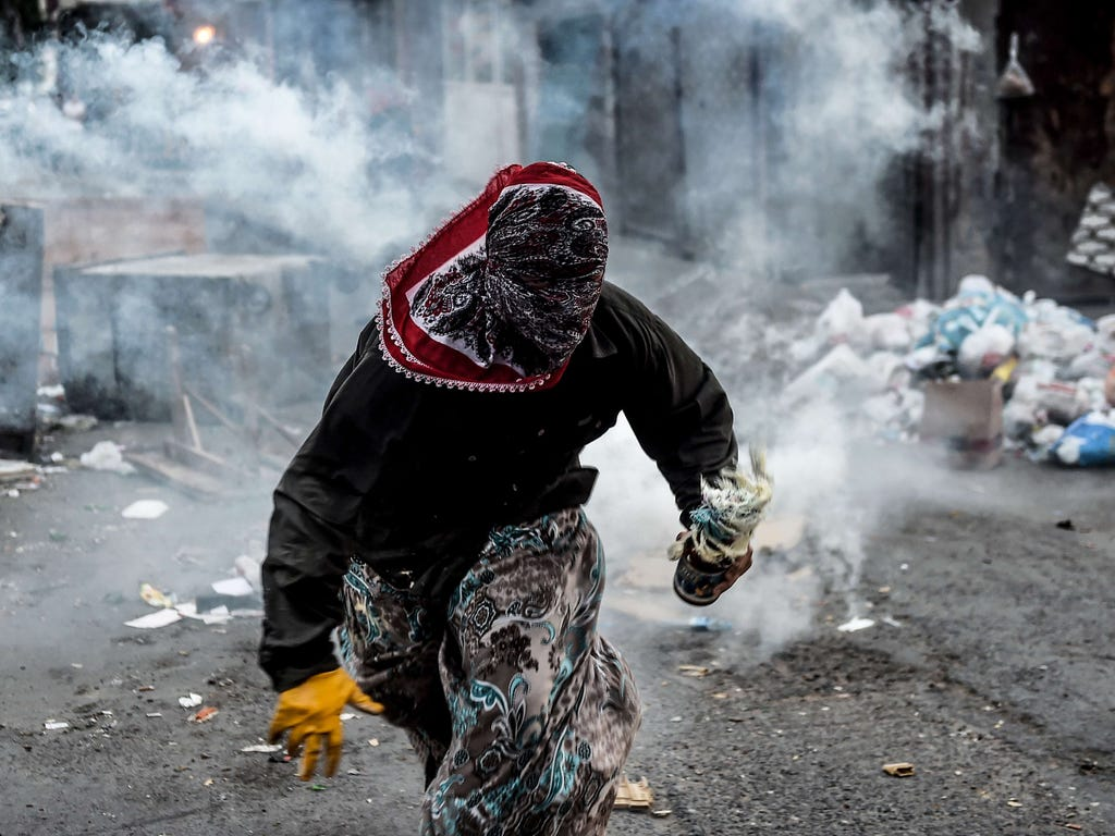 A masked Kurdish militant holds a molotov cocktail while he runs away from a tear gas cannister during clashes with Turkish police in the Gazi district of Istanbul.
