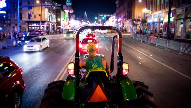 Curtis Carney, owner, drives his tractor down Broadway during a ride on the Off The Wagon Tour in Nashville, Tenn., Tuesday, July 18, 2017.
