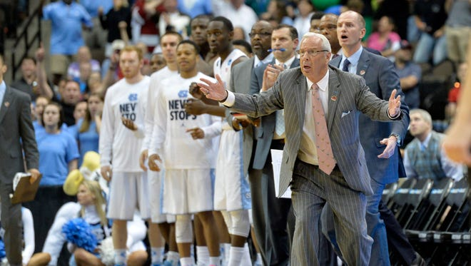 North Carolina Tar Heels head coach Roy Williams and the Tar Heel bench watch the closing seconds in the second half of a game against the Harvard Crimson in the second round of the 2015 NCAA Tournament at Jacksonville Veteran Memorial Arena. North Carolina won, 67-65.