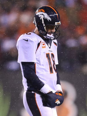 Peyton Manning walks off of the field after throwing an interception to Dre Kirkpatrick of the Cincinnati Bengals during the fourth quarter at Paul Brown Stadium on Dec. 22, 2014 in Cincinnati, Ohio.
