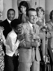 Entertainer Sammy Davis Jr. hugs President Richard Nixon from behind as Nixon addresses about 8,000 supporters at a youth rally in Miami, Aug. 22, 1972.  Davis' apparently spontaneous gesture came shortly after the president had been nominated for reelection by the Republican National Convention.