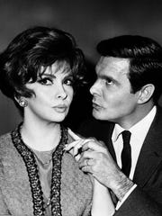 "Gina Lollobrigida and Louis Jourdan hold hands as they act out a scene from the film ""The Sultans"" in a Studio in Paris, France, March 1, 1966. The Italian actress stars as a photographer in the film which is a modern study of married life. The film co-stars Jourdan and Corinne Marchand and is directed by Jean Delannoy. (AP Photo/Michel Lipchitz)"