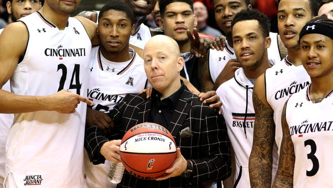 University of Cincinnati head coach Mick Cronin and players celebrate his 300th win.