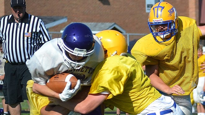 Oconto's defense tackles a Marinette player in a scrimmage on Friday.
