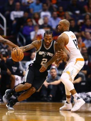 Dec 15, 2016; Phoenix, AZ, USA; Spurs forward Kawhi Leonard (2) drives to the basket against Suns forward P.J. Tucker (17) at Talking Stick Resort Arena. The Spurs defeated the Suns 107-92.
