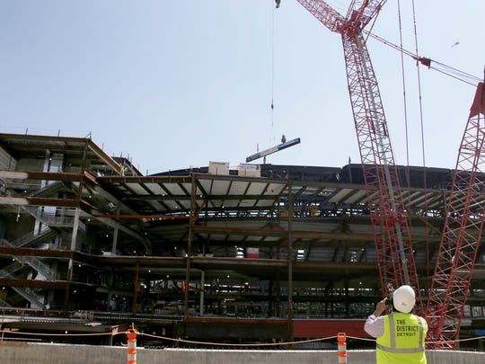 """Olympia Development holds the """"topping off"""" ceremony at the Little Caesars Arena in downtown Detroit on Thursday, August 4, 2016 where ironworkers hoist the final beam into place."""