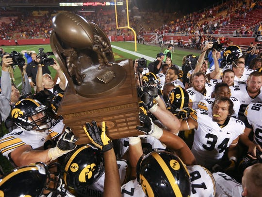 Iowa players hoist the Cy-Hawk Trophy after beating Iowa State, 27-20, on Saturday, Sept. 15, 2013, at Jack Trice Stadium in Ames.
