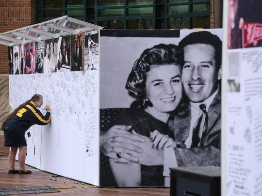 Faye Perdue of Allen Park leaves a message on boards put up for the community in memory of the late Mike Ilitch on Wed., February 15, 2017 outside of Comerica Park in downtown Detroit.