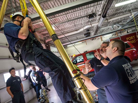 Port Huron Fire Lt. Kurt McFarlane, center, walks recruits Cody Gordon, left, and Peter Lafata through a confined space rescue training Nov. 14.