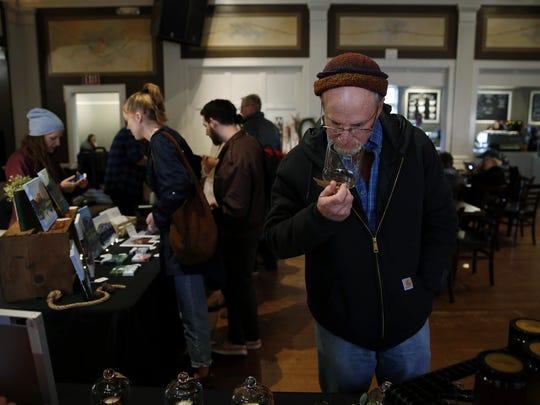 Edward Epifani of Salem smells an Arcane Chemistry candle scent during a pop-up event at Ike Box in Salem, Oregon, Saturday Nov. 25, 2017.