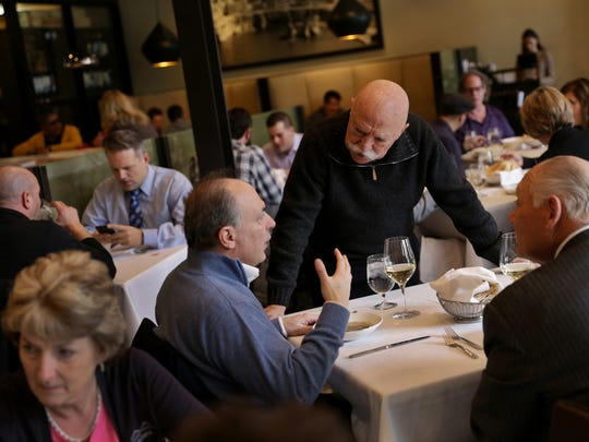Phoenicia restaurant owner Sameer Eid talks with customers during lunch at the Birmingham eatery on Thursday, February 8, 2018.