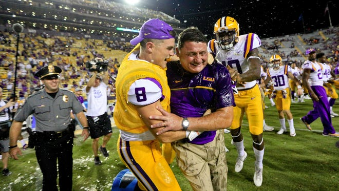 LSU interim head coach Ed Orgeron is dunked with a cooler by quarterback Caleb Lewis (8) and wide receiver Stephen Sullivan (10) following a win against Missouri.