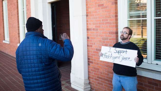 Clemson faculty member Chenjerai Kumanyika takes a photo of his colleague Mikel Cole showing support Monday in Clemson for a fast protesting President Donald Trump's travel ban and pressing the university to speak out against the president's executive order.