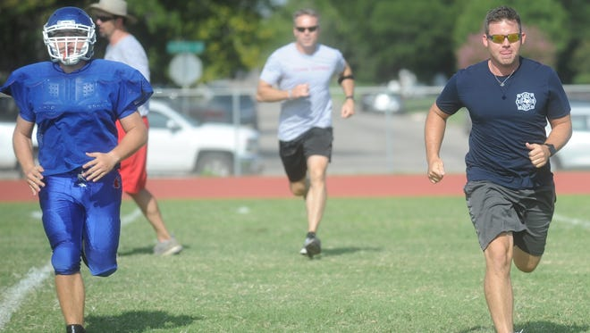 Abilene police officer Trent Farmer, right, and Police Chief Stan Standridge run with the Cooper football team during practice Saturday, Aug. 19, 2017.