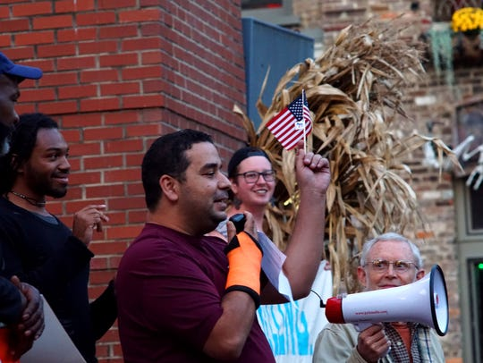 Yassin Terou waves an American flag while addressing the crowd at a protest of the latest version of President Trump's travel ban on Oct. 18, 2017.