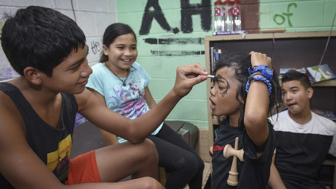 Volunteer Aidan McDonald, 13, paints the face of Matthew Rivera, 11, at the Agana Heights summer camp on June 16.