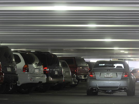 A motorist drives slowly in a lane in the parking garage