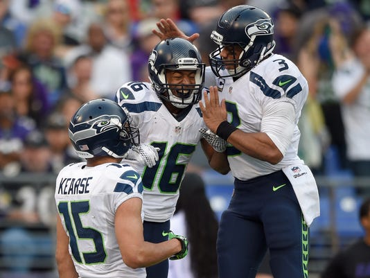 Seattle Seahawks wide receiver Jermaine Kearse (15) watches as Seahawks wide receiver Tyler Lockett (16) and Seahawks quarterback Russell Wilson (3) celebrate connecting for a touchdown during the second half an NFL football game against the Baltimore Ravens, Sunday, Dec. 13, 2015, in Baltimore. (AP Photo/Nick Wass)