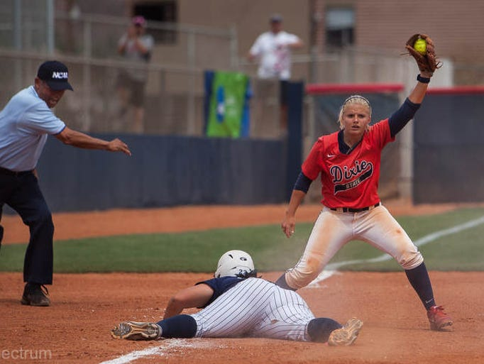 Dixie State's Brooke Budge holds up the ball as the official signals Cal State's Nicole Pires out, ending the game at Karl Brooks Field on Saturday, May 17, 2014.