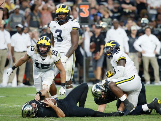 Chase Winovich (15) and Mike McCray (9) react after