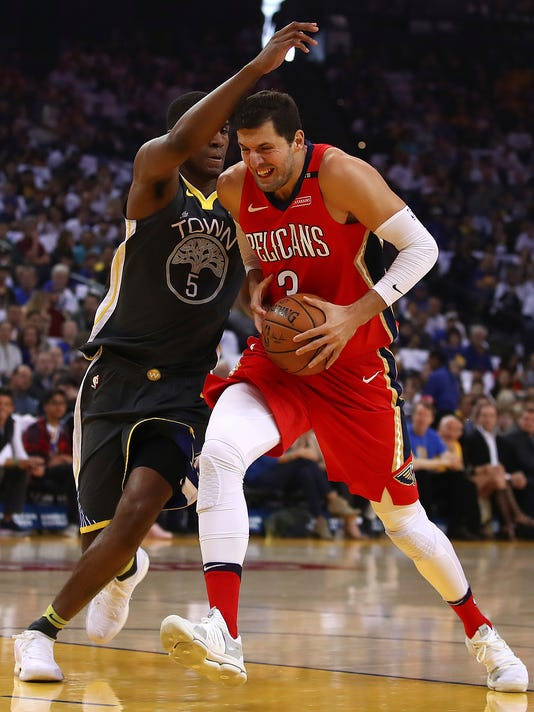 New Orleans Pelicans' Nikola Mirotic, right, drives the ball against Golden State Warriors' Kevon Looney (5) during the first half of an NBA basketball game Saturday, April 7, 2018, in Oakland, Calif. (AP Photo/Ben Margot)