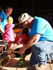 A volunteer works with a boy that attended AgriVenture