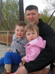 Joe Dunn holds his children, Joey and Shiloh.