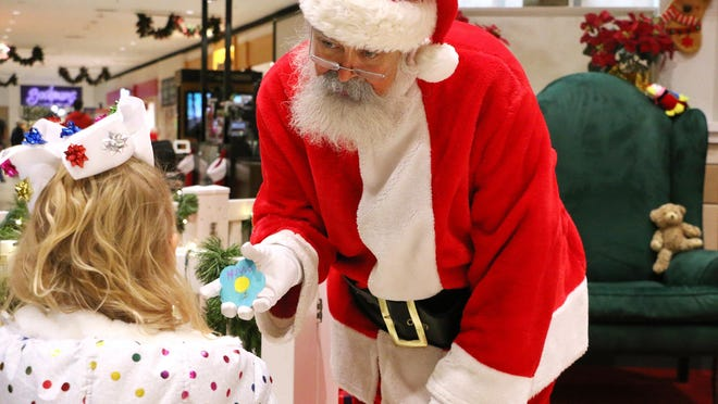 Hadlie Orr, Hays, gives Santa a painted flower while visiting him last year at Big Creek Crossing in Hays. Santa will still appear on Friday with extra precautions in place.
