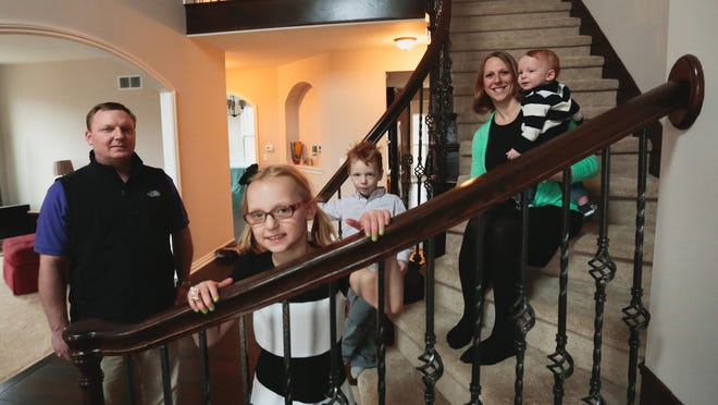 Mike and Amy Perlman with their children Samantha, 6, Beckett, 3, and Trevor, 1, on the staircase of the new four-bedroom brick home they built in South Lyon.