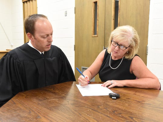 District Court Judge Jason Duffy, left, watches as Joan Vickers signs paperwork making her appointment as Marion County sheriff official on Monday.