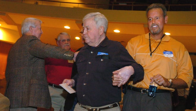 In this file photo, former Lee High School football coach Tom Jones is patted on the shoulder by former player Ben Wood, left, while Jones' son Tom Jones, Jr. helps him to his seat Saturday, Dec. 9, 2006 at an event to honor his time at the school. (Montgomery Advertiser, Karen S. Doerr)