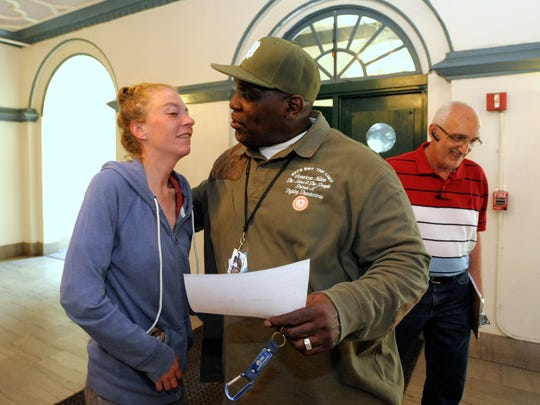 Apartment resident Brittney Schuholz, 26, talks with NSO case manager James Carey. The tent city shed new light on aid challenges in Detroit.