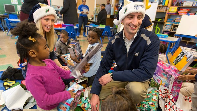 Brewers GM David Stearns and his fiancée Whitney Ann Lee hand out presents to pupils at Bruce Elementary School in Milwaukee.