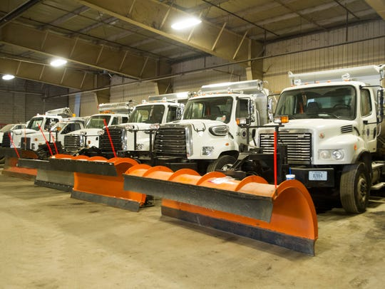 Snow plows wait inside a city garage filled with salt