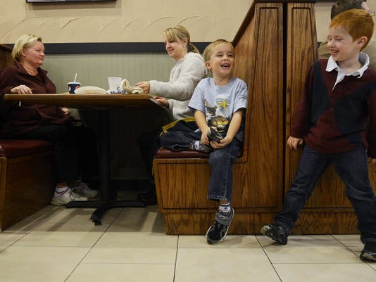 Nathan Frome, 5, of York Township, right, jokes with his kindergarten classmate Hayden Koons, 5, also of York Township, as Lisa Little, left, and Hayden's mother, Dawn Koons, chat over pizza at Nittany Pizza in York Township.