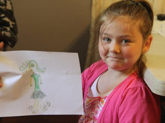 Peyton, 10, poses with one of her drawings. She excels