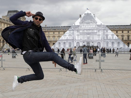 Street artist JR poses in front the Louvre Pyramid in Paris, Tuesday, May 24, 2016. For his latest bold project, street artist JR is creating an eye-tricking installation at the Louvre Museum that makes it seem as if the huge glass pyramid at the heart of the courtyard has disappeared.