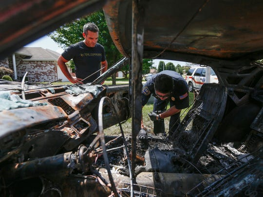 Brett Welcome, left, watches Fire Marshal Ben Basham as he investigates a fire that destroyed the Mach I Mustang parked in his driveway.
